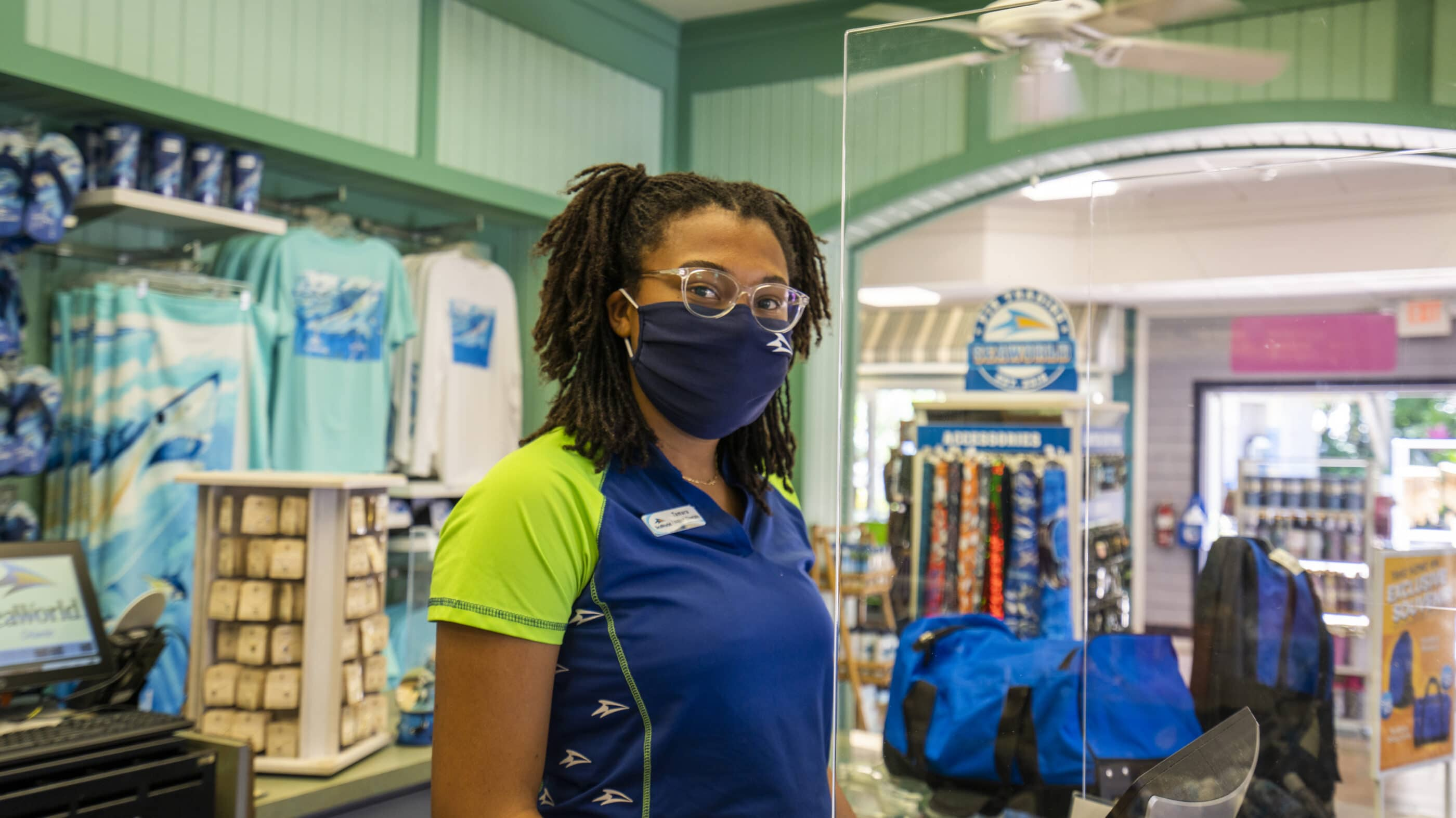 A SeaWorld San Diego employee with a mask behind plexiglass in a retail outlet.