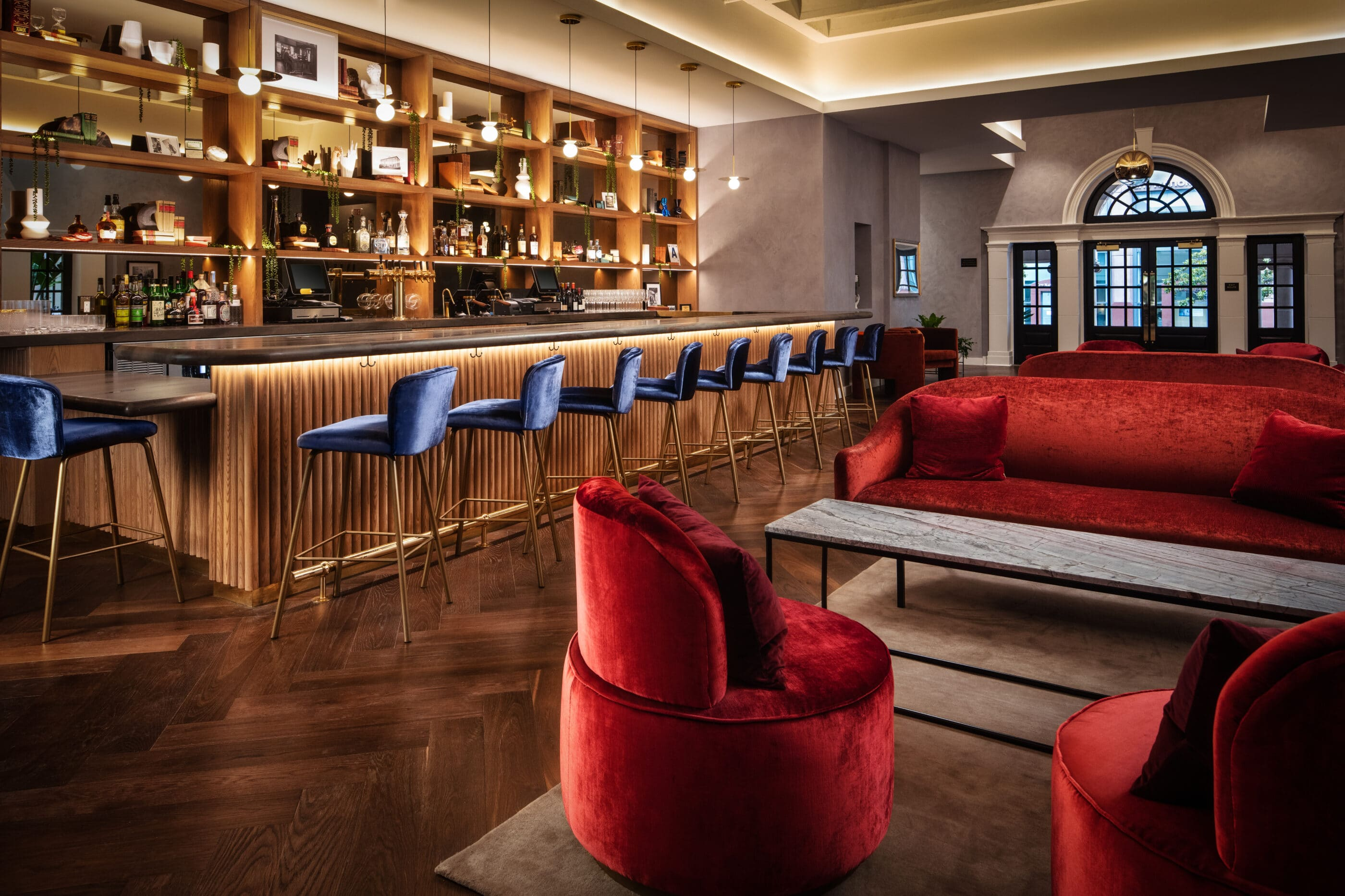 Red velvet couches and blue barstools in The Guild Bar.