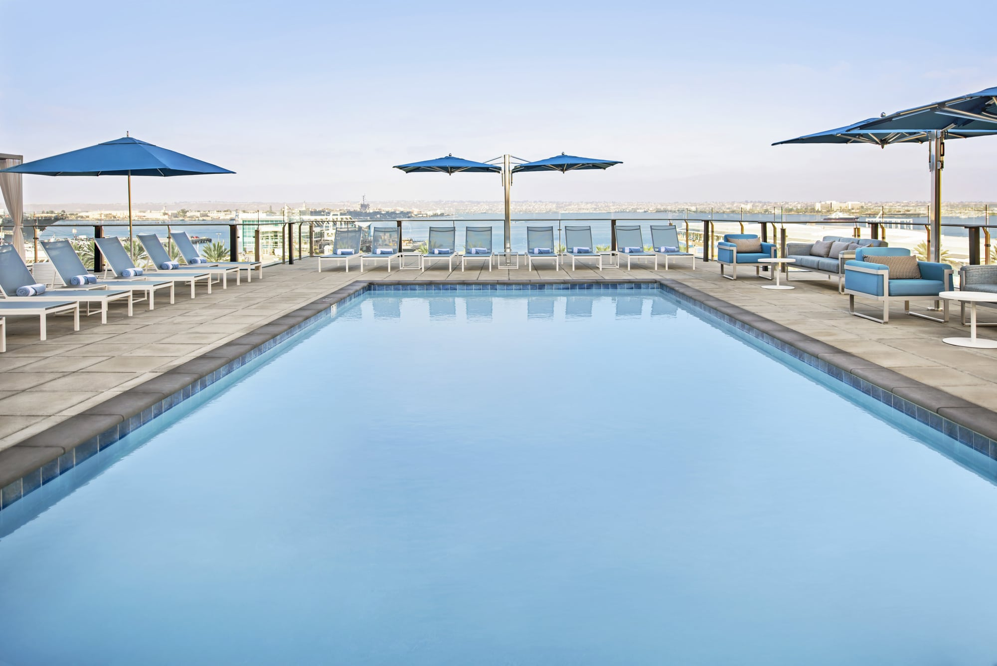 Open-air pool deck surrounded by lounge chairs, overlooking San Diego Bay.
