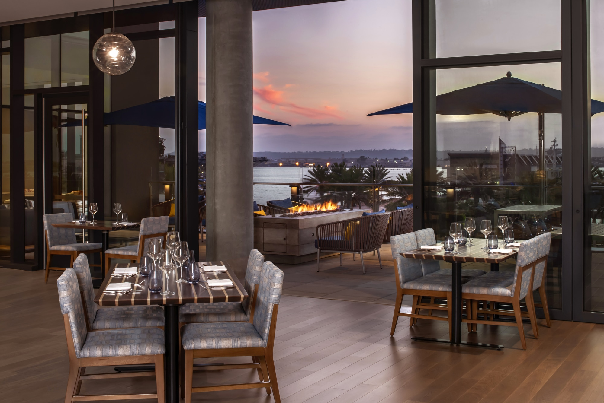 Tables in Vistal Restaurant overlook the San Diego Bay at sunset.