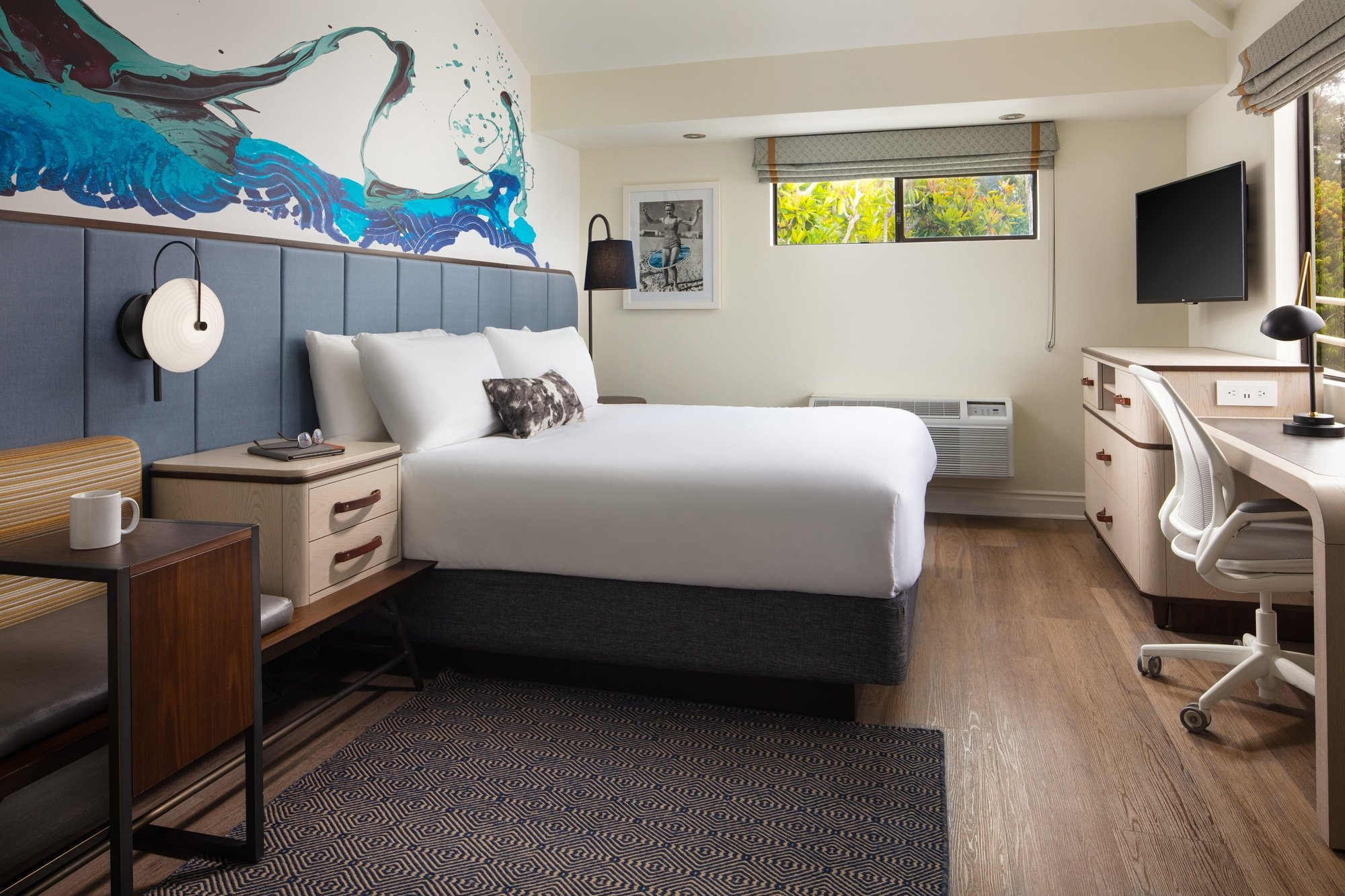 A king bed room with a beach theme of grey and neutral colors with blue wave art on the wall.