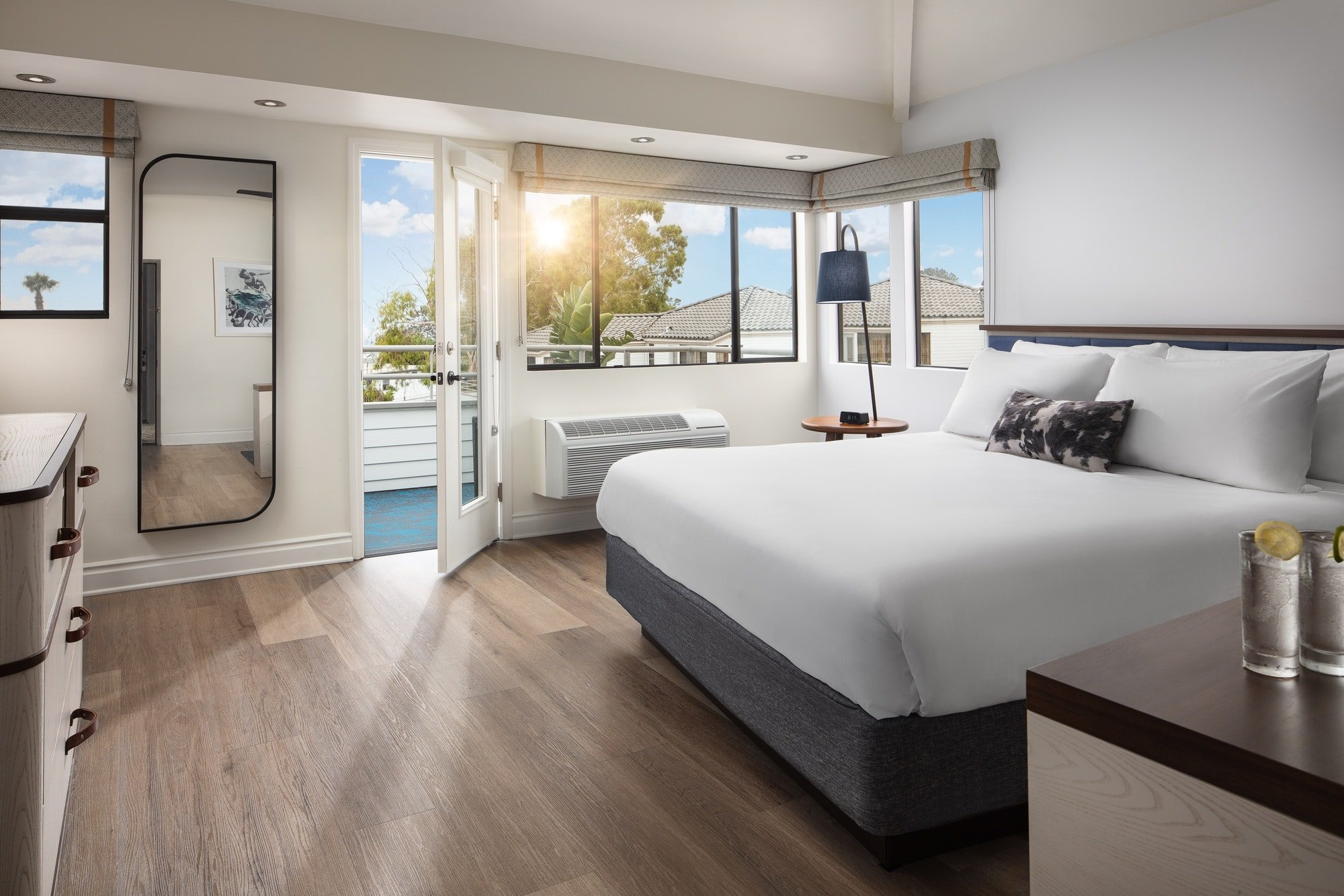 A king bed inside of an ocean view suite at Hotel Indigo Del Mar