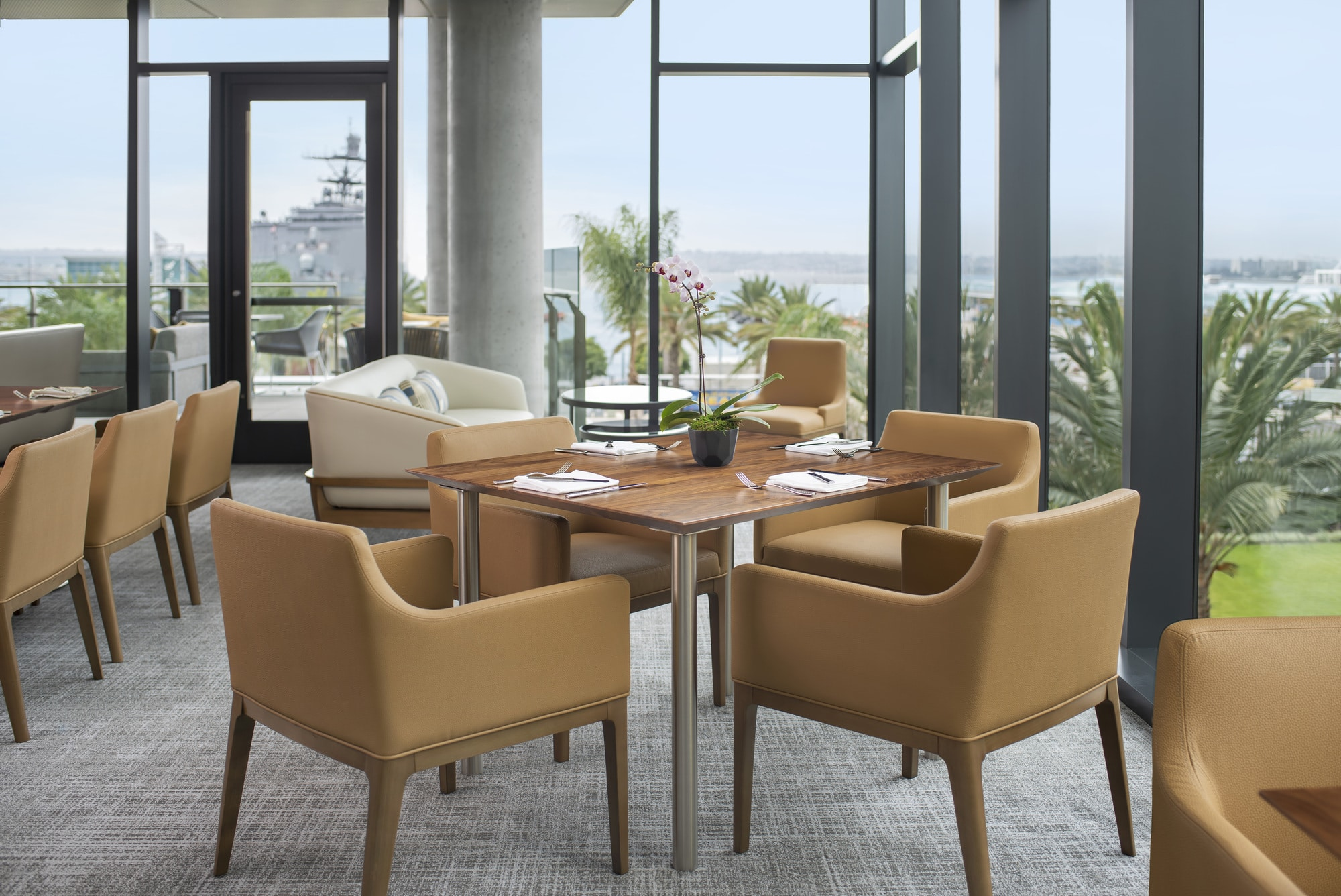 Tables in the Club Lounge set against tall glass walls with views overlooking the bay.