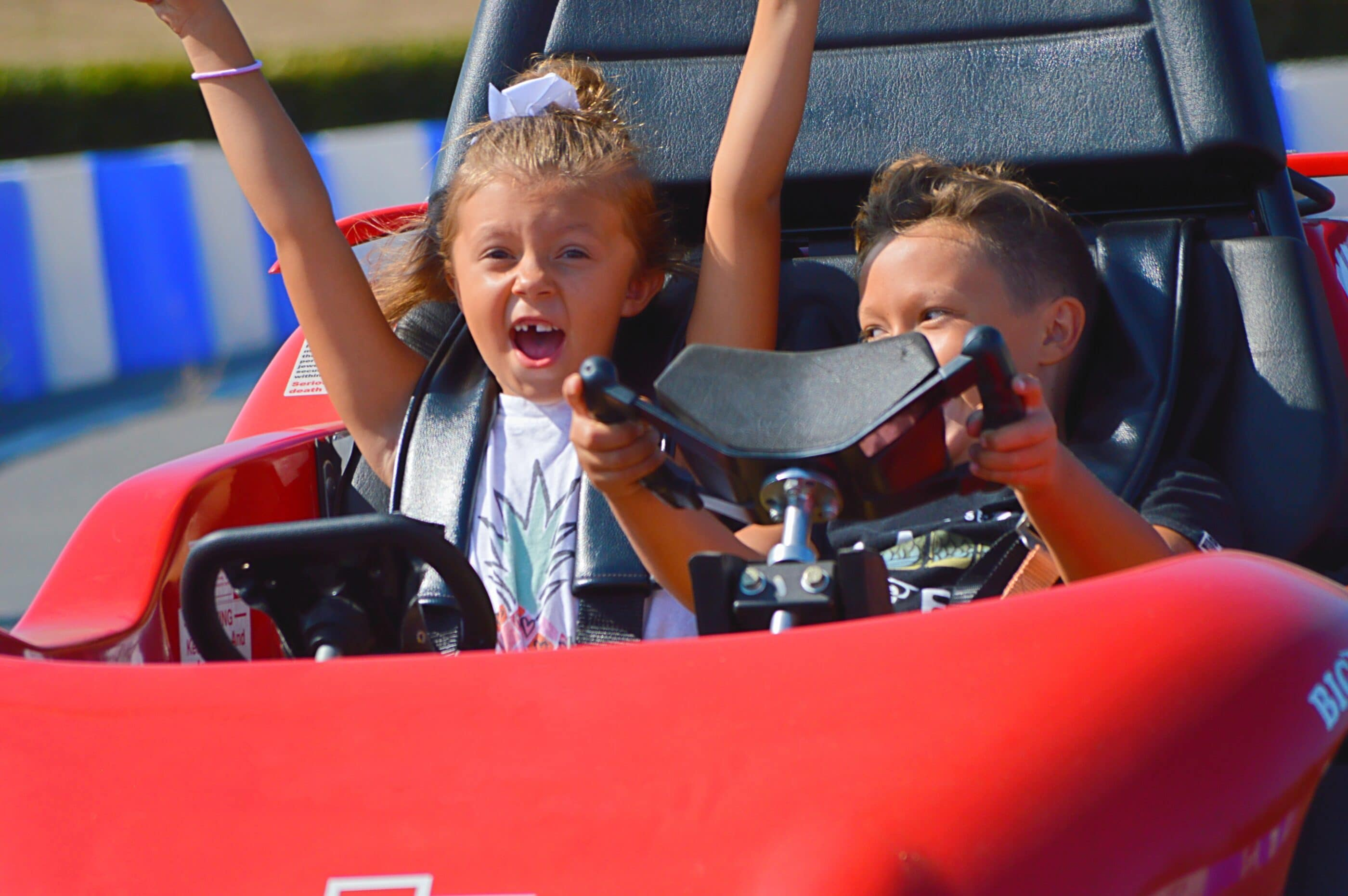 Two girls drive the Go Karts at Belmont Park San Diego