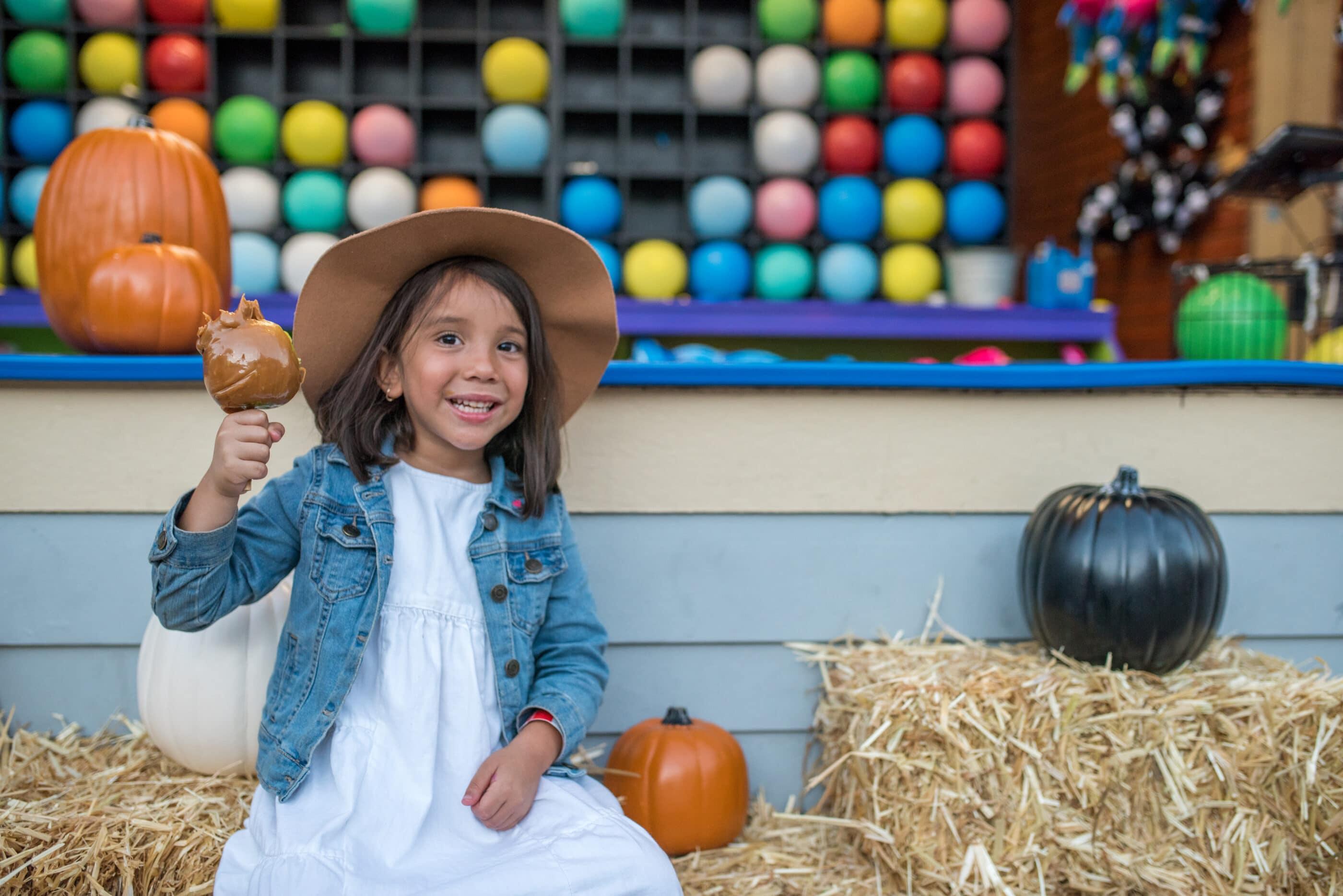 A girl eats a candy apple at Harvest Walk.