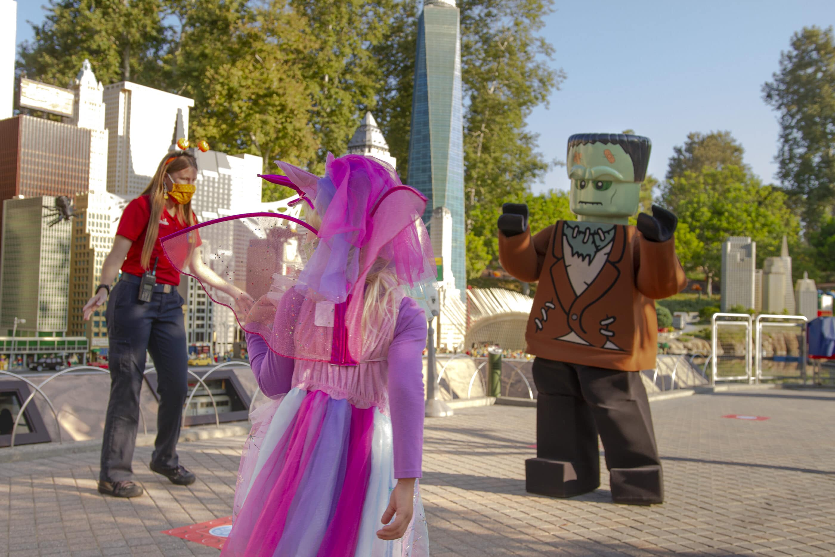 A girl in a costume walks up to a staff member dressed as Frankenstein in Miniland.