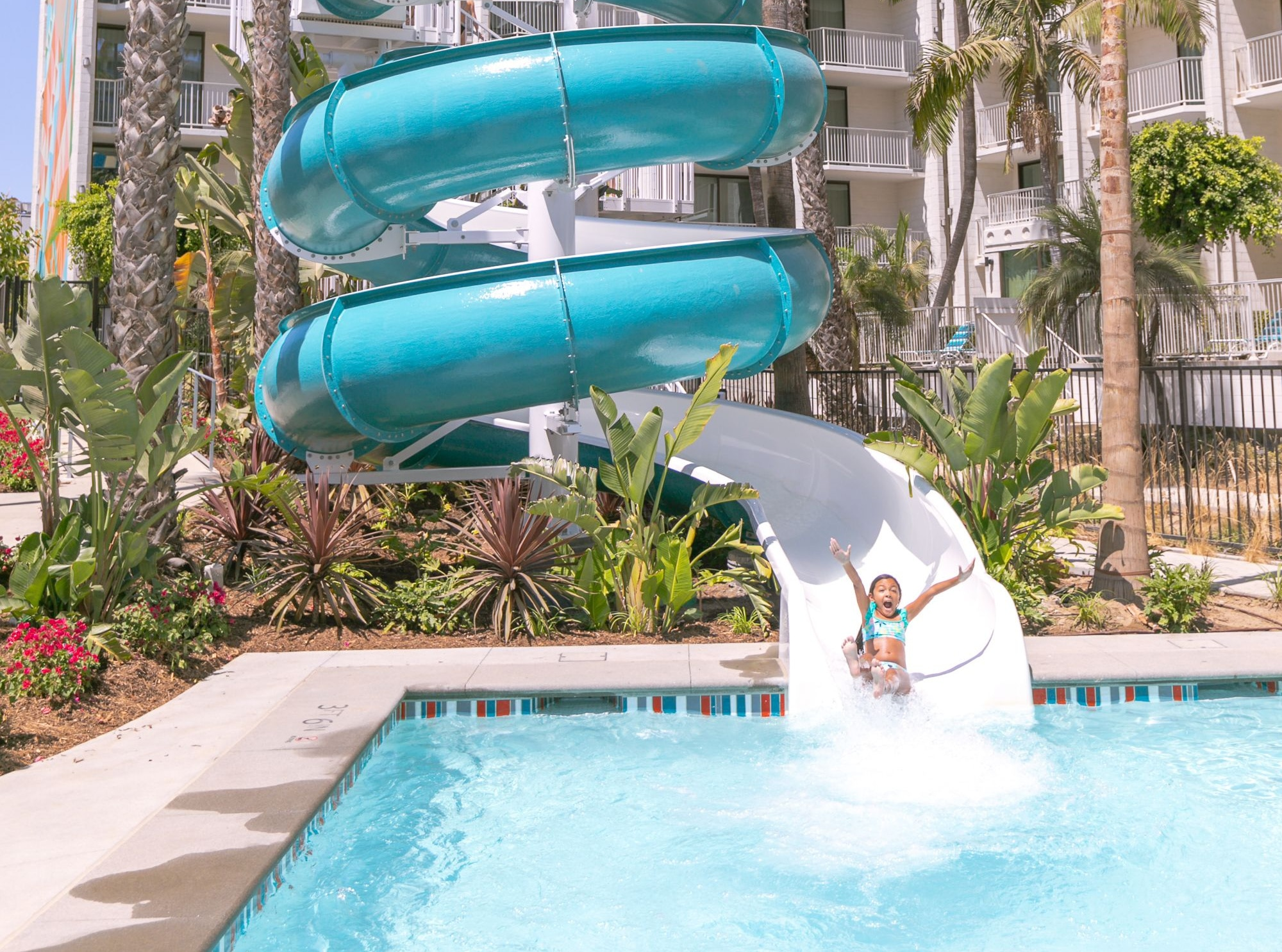 A little girl rides down the water slide into the swimming pool.