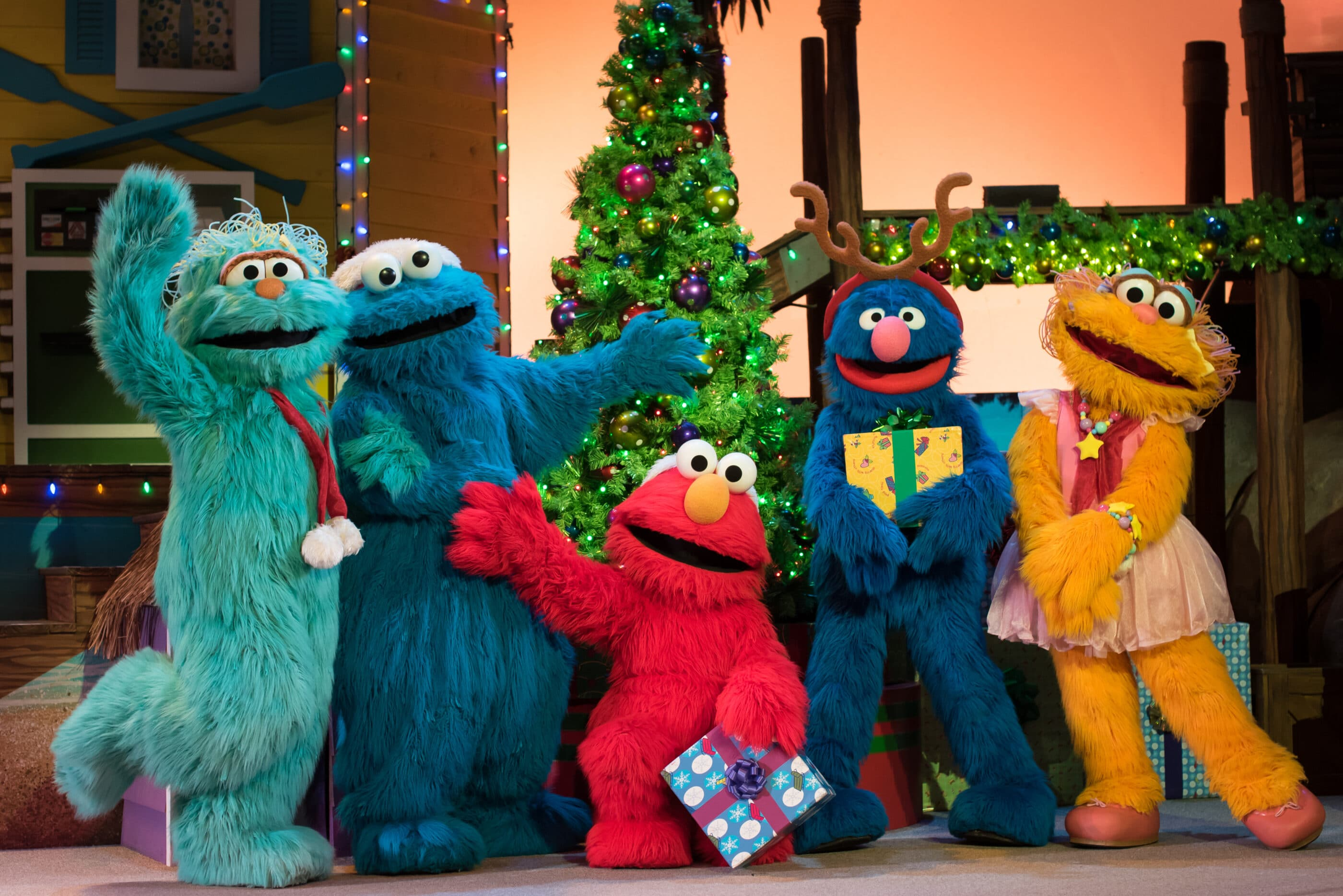 Elmo and friends hold presents in front of a Christmas tree.