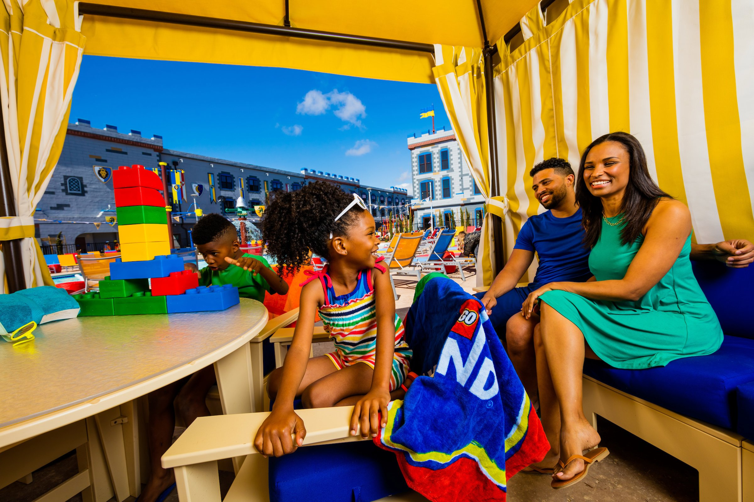 A family gathers in a cabana near the swimming pool at LEGOLAND Castle Hotel.