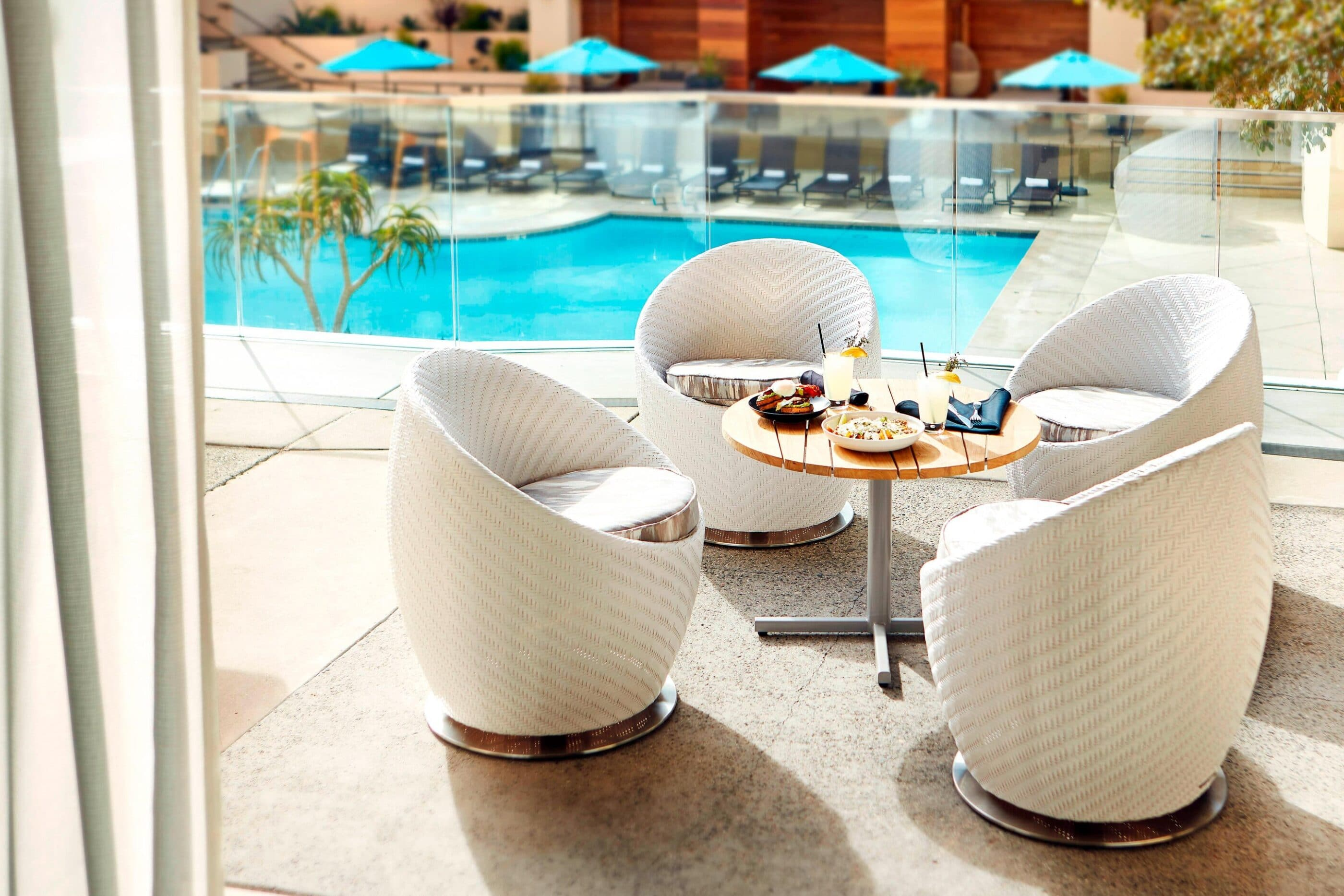 A seating area with food and drinks on the table near the outdoor swimming pool.