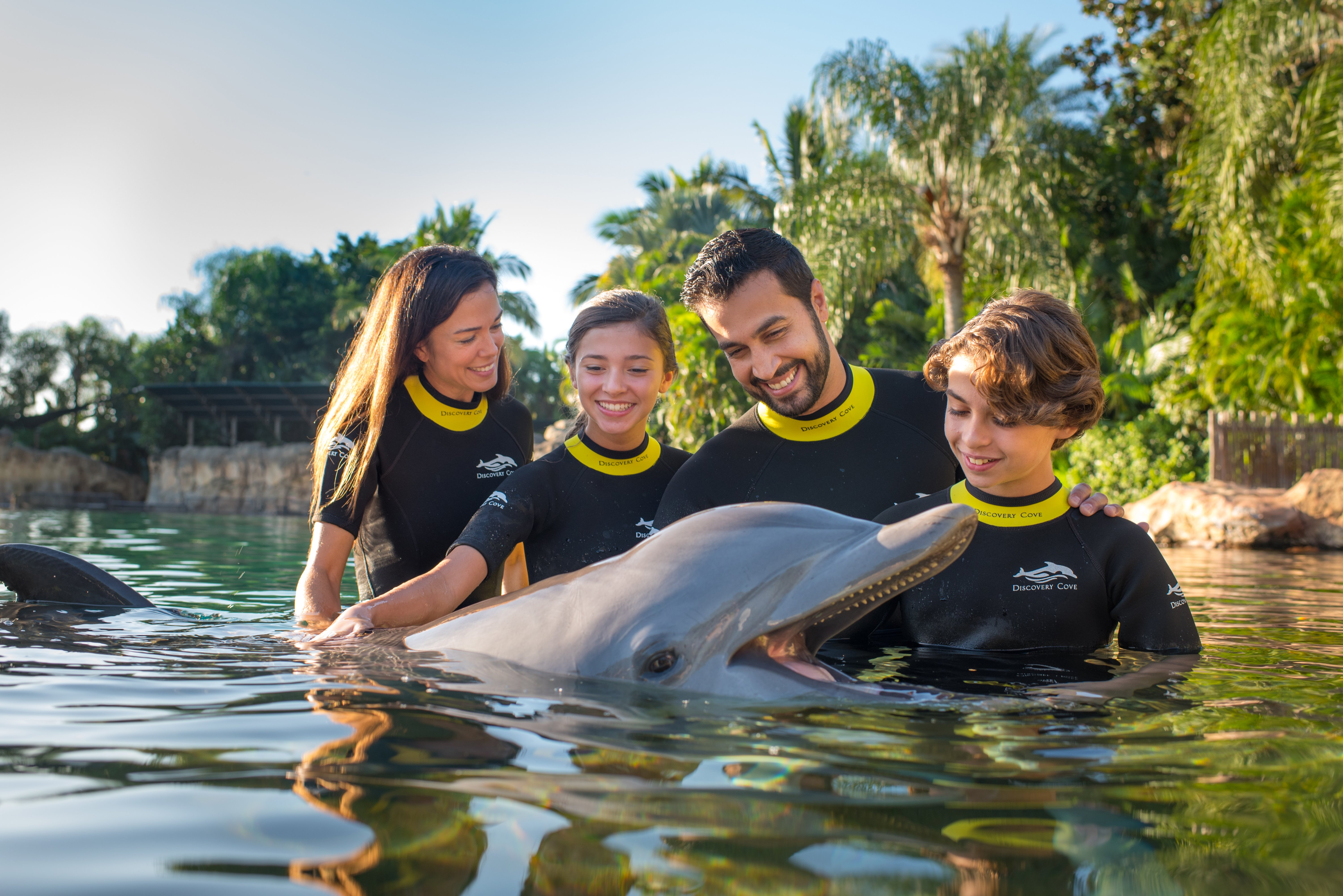 A family poses with a bottlenose dolphin in the water at Discovery Cove.