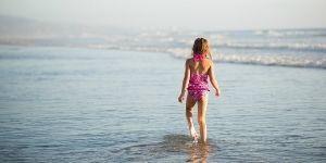 Girl walks into the ocean on a San Diego beach.