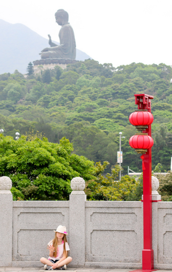 My daughter sits near a lantern with the Hong Kong Big Buddha in the background.