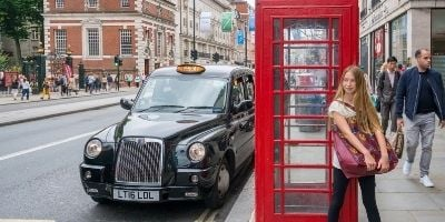 My daughter stands in front of a red London phone booth as a taxi drives by.
