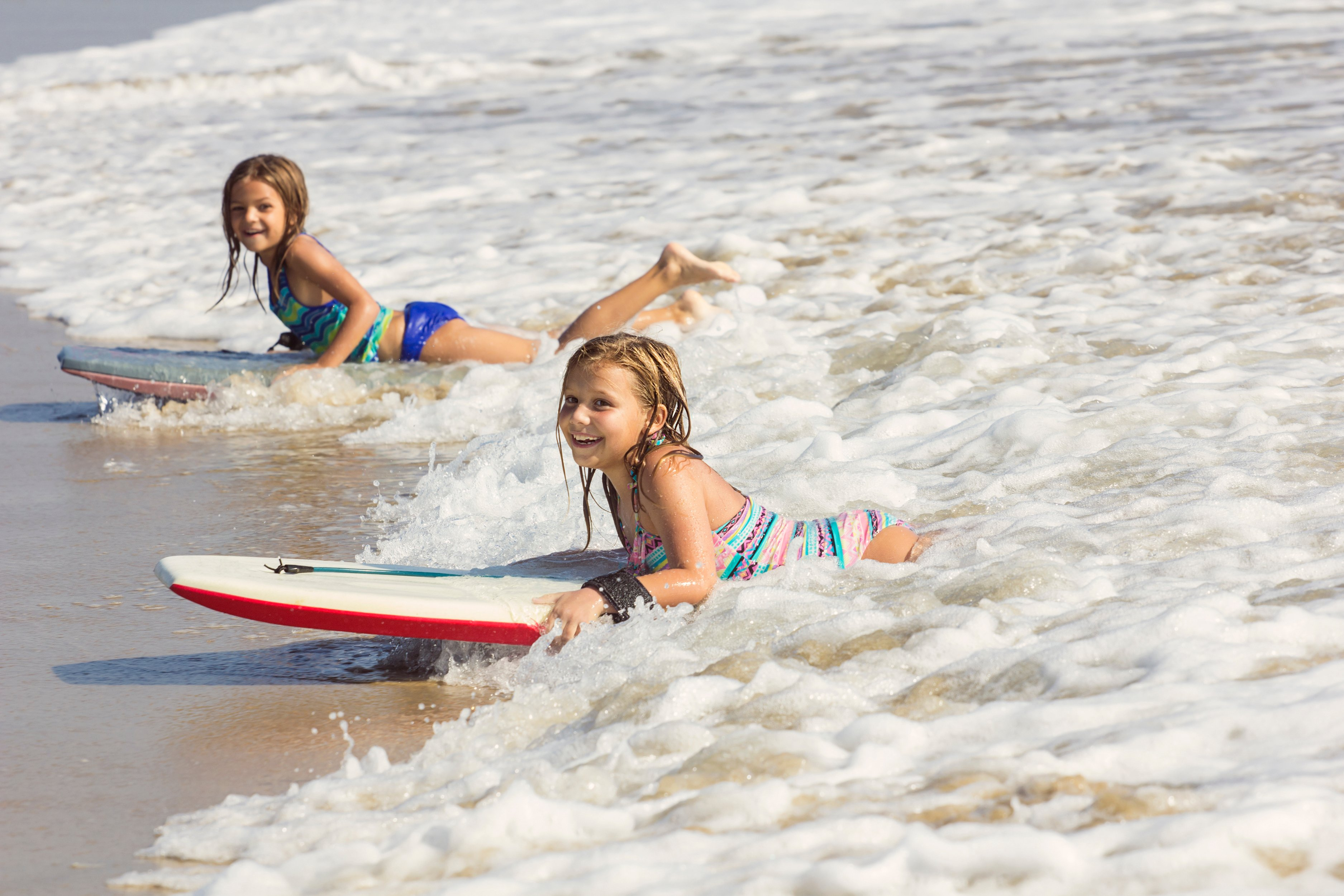 Two girls ride boogie boards into shore on a California beach.