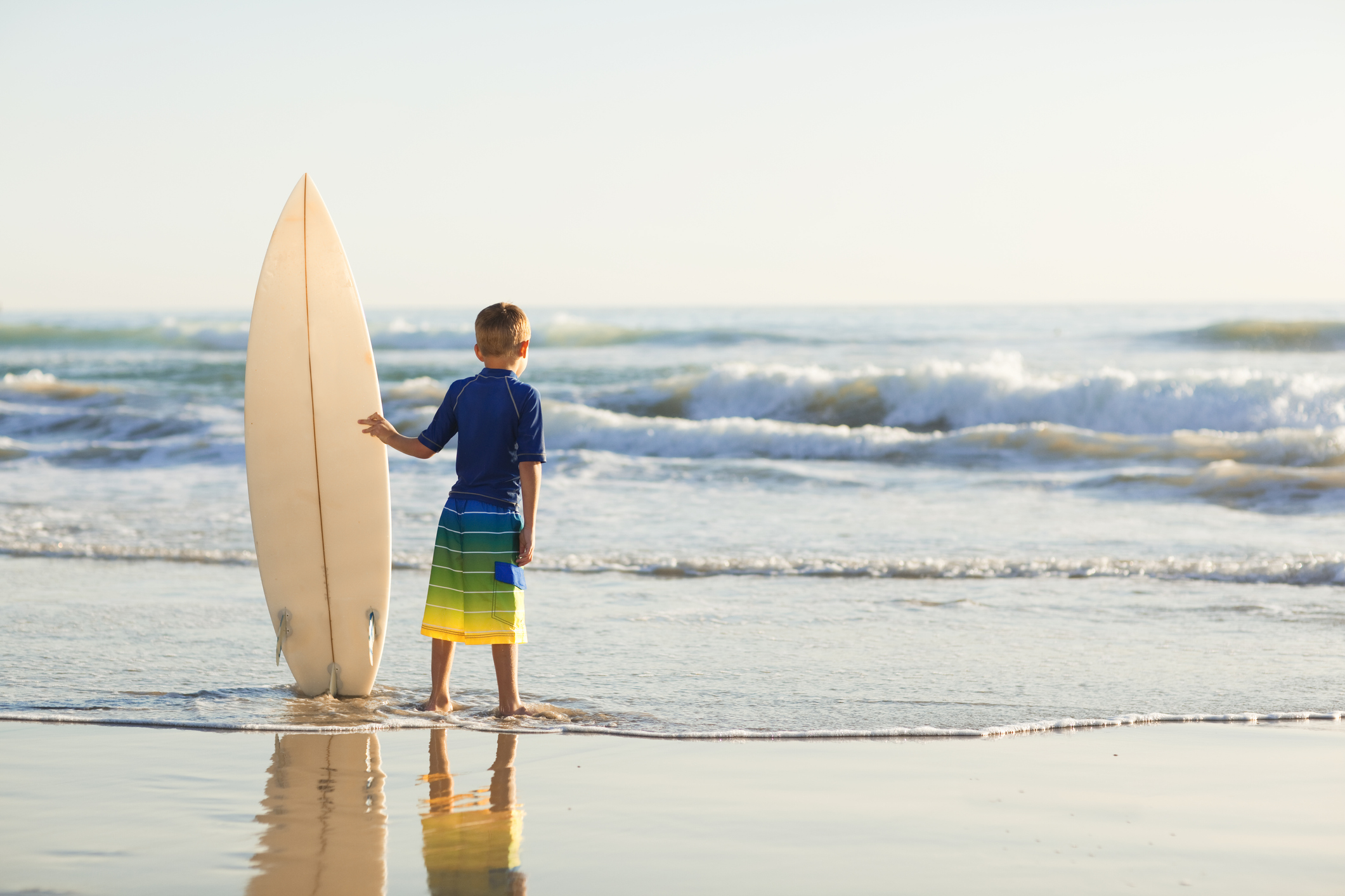 A little boy holds a surfboard on a California beach.