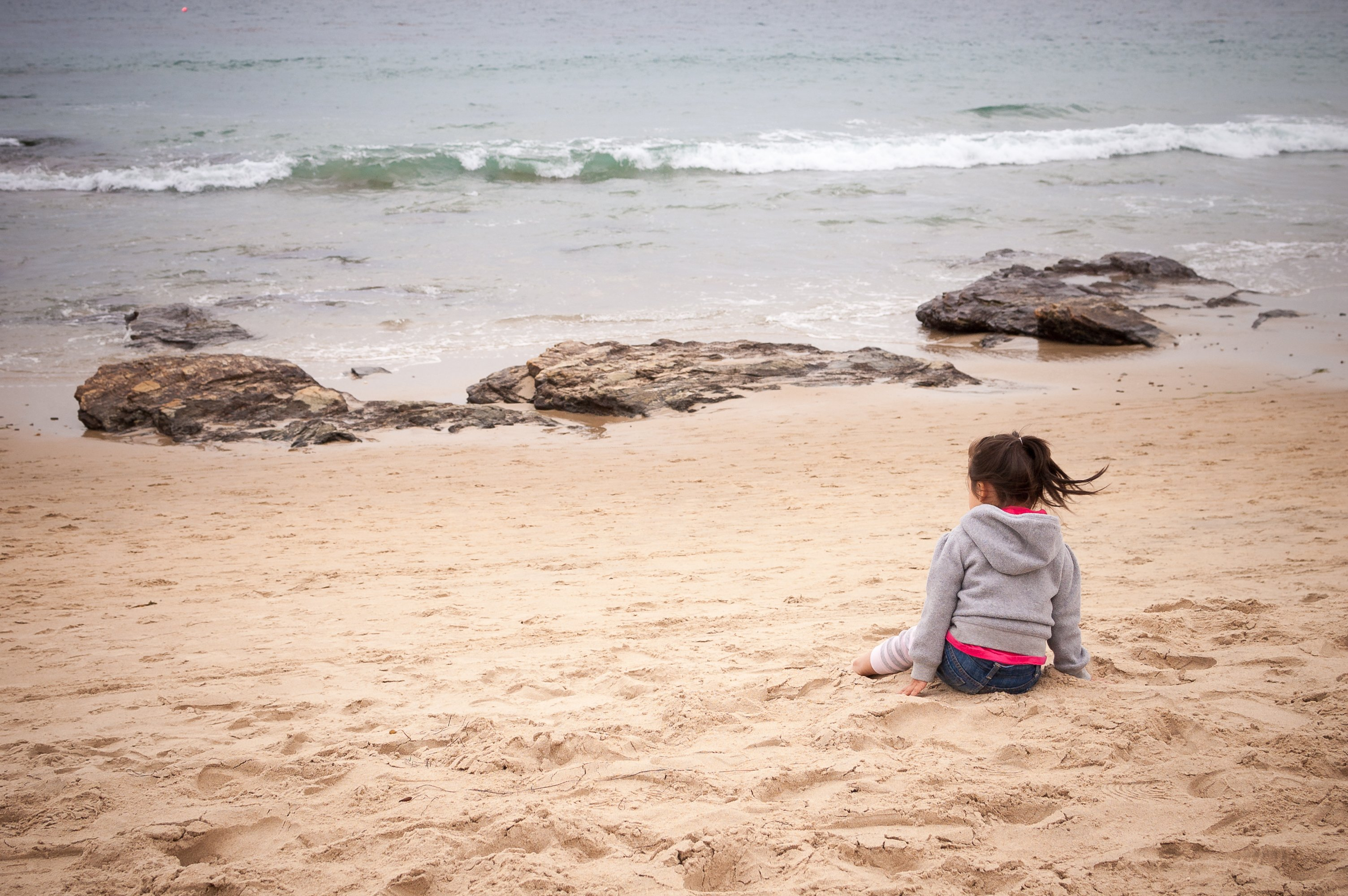 A little girl sits on the beach at Crystal Cove State Park.