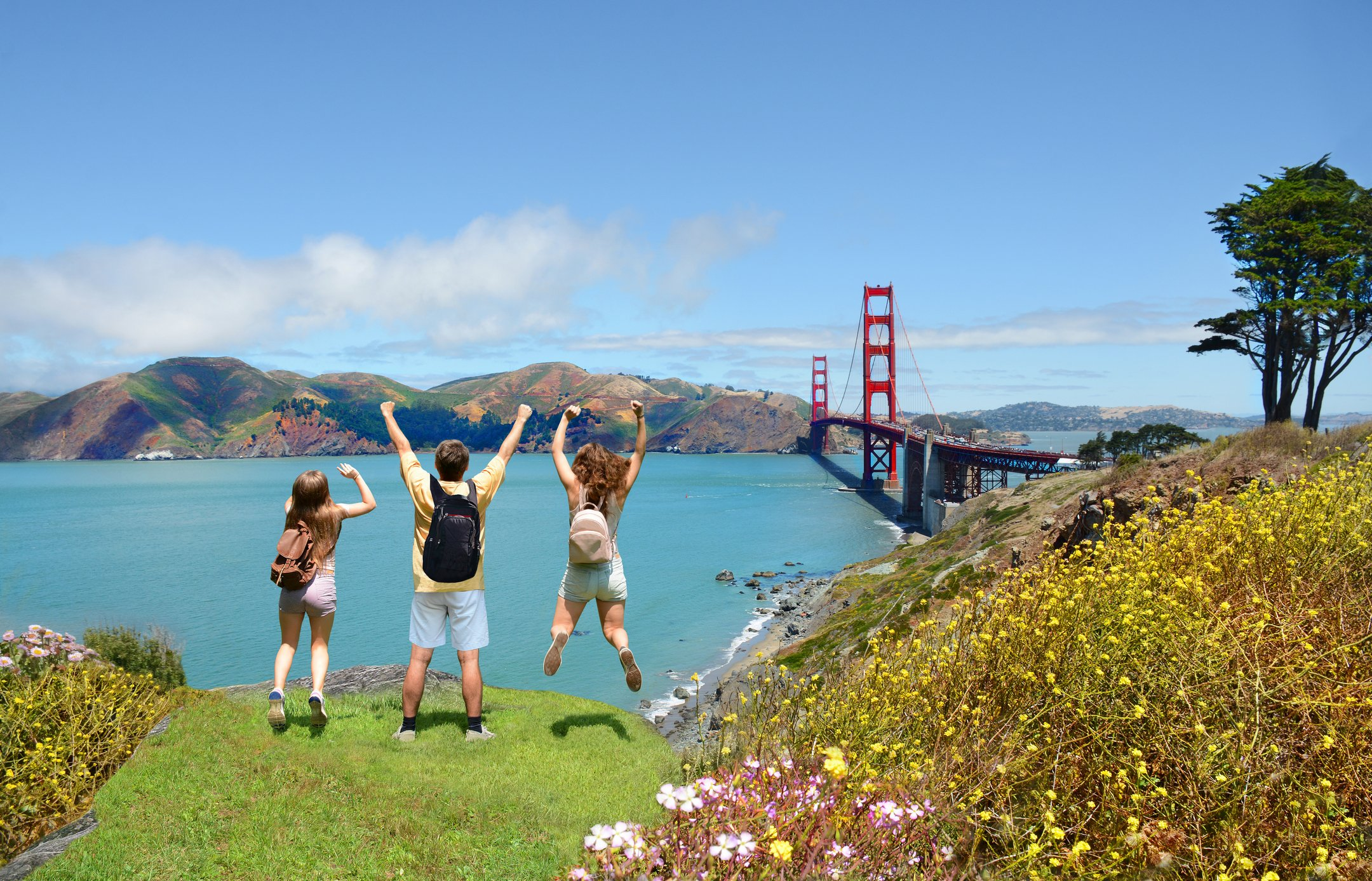 A family jumps in the air near the Golden Gate Bridge.