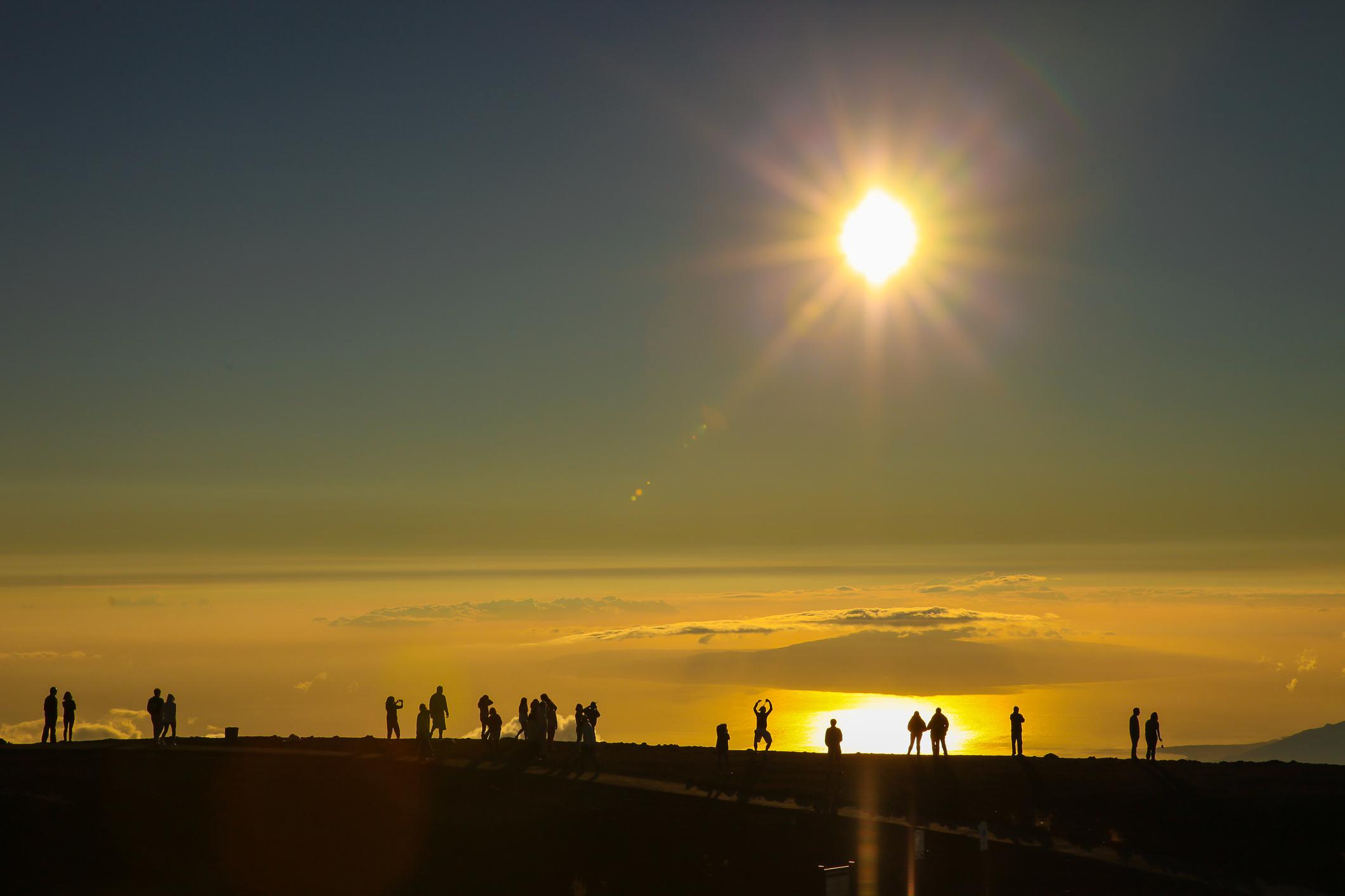 People watch sunrise at Haleakala volcano in Maui