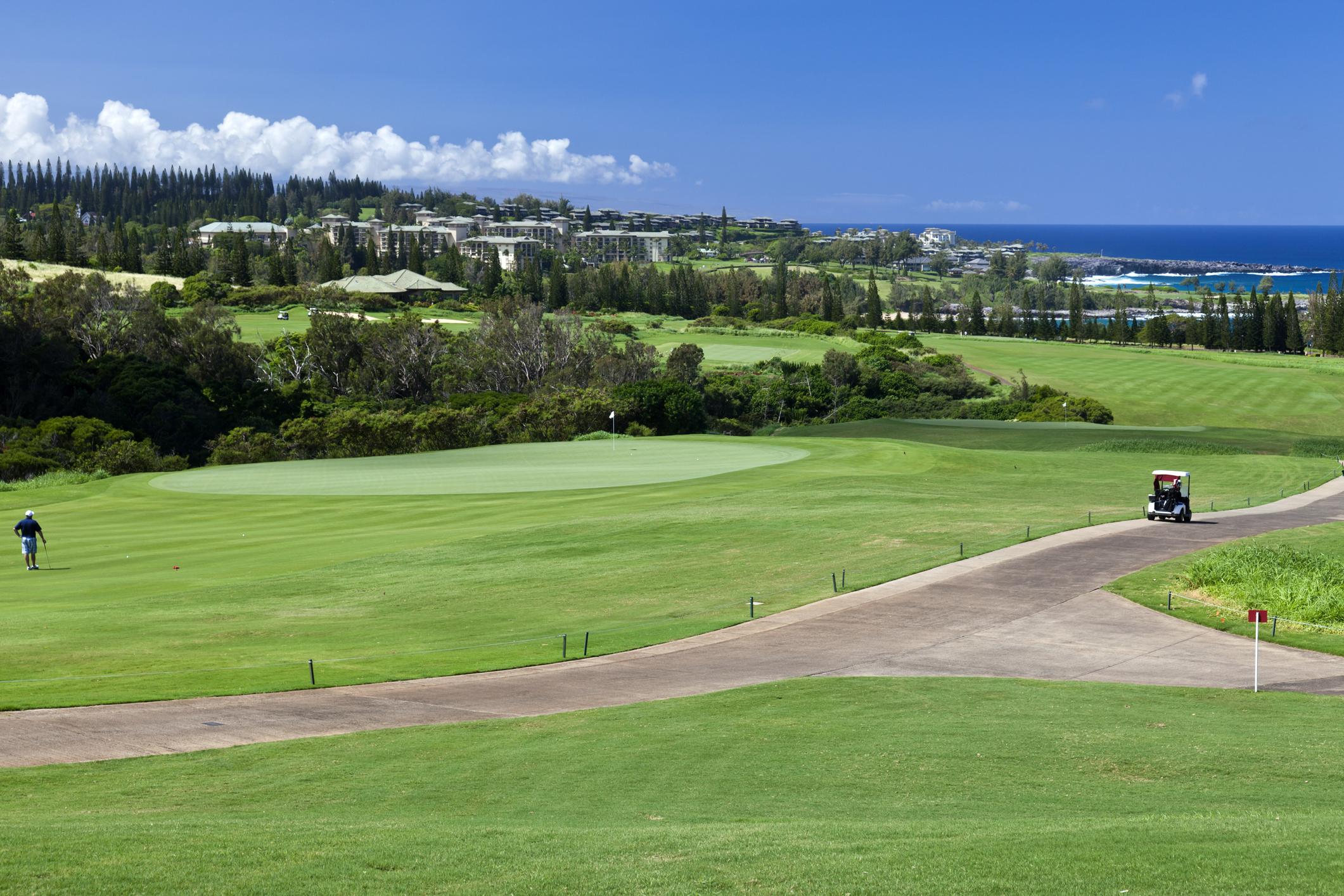 A golf cart drives along an oceanfront golf course in Kapalua.
