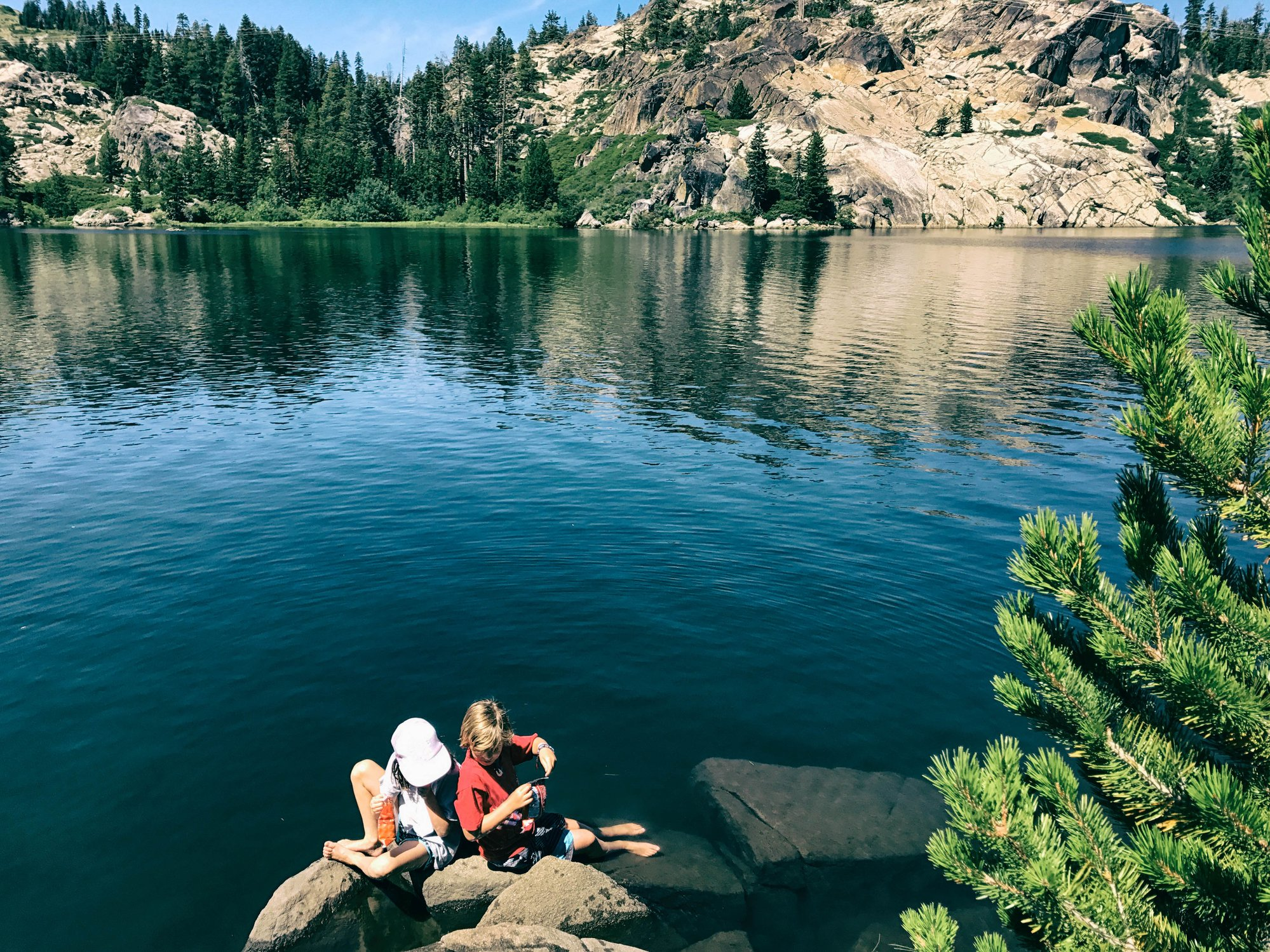 Two kids play by the water at Lake Tahoe.