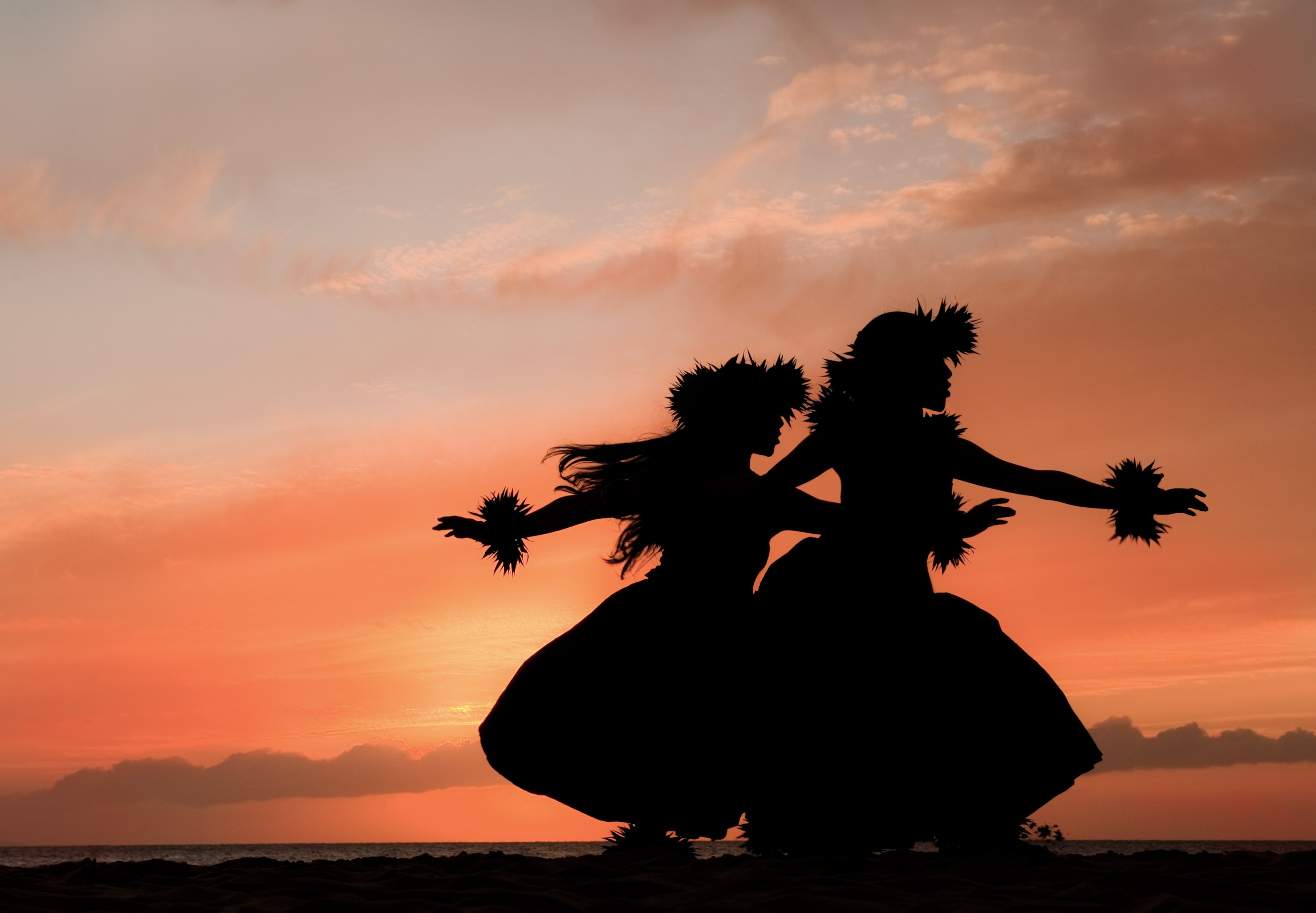Shadow of two hula dancers against a glowing tropical sunset in Maui.