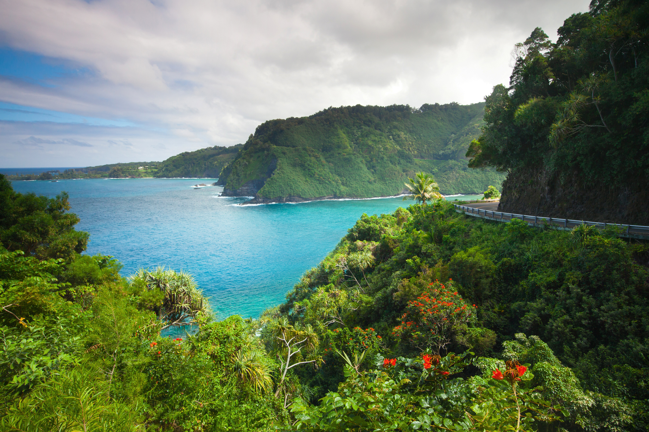 A narrow part of the road to Hana hugs the cliffside near the ocean.