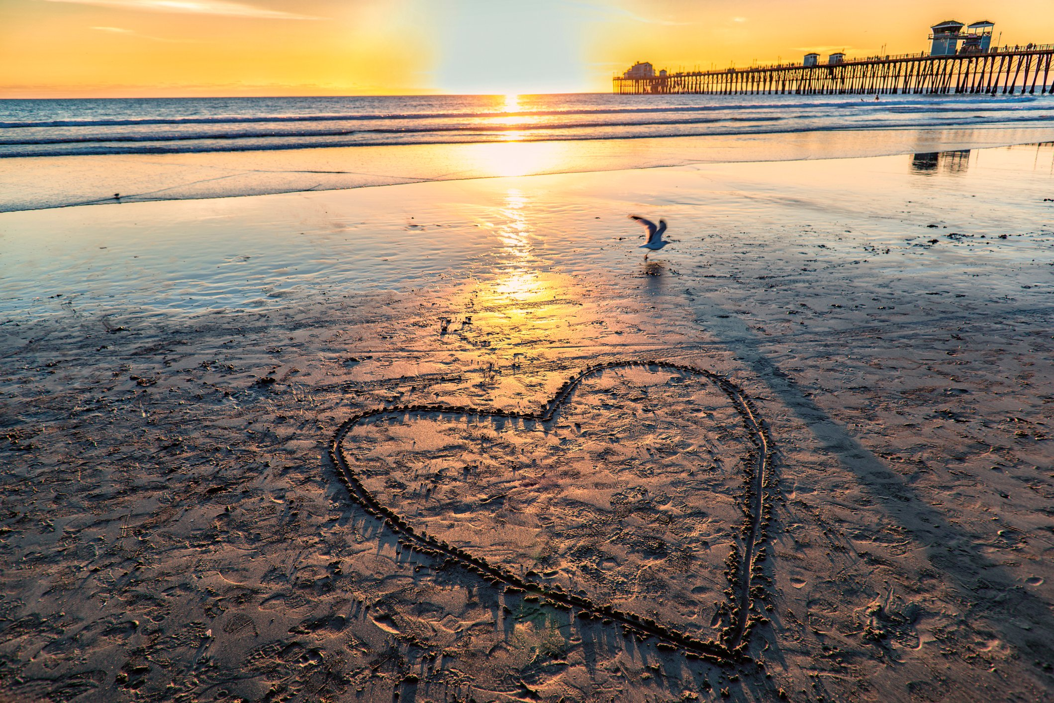 A heart drawn in the sand on Oceanside beach near the pierl
