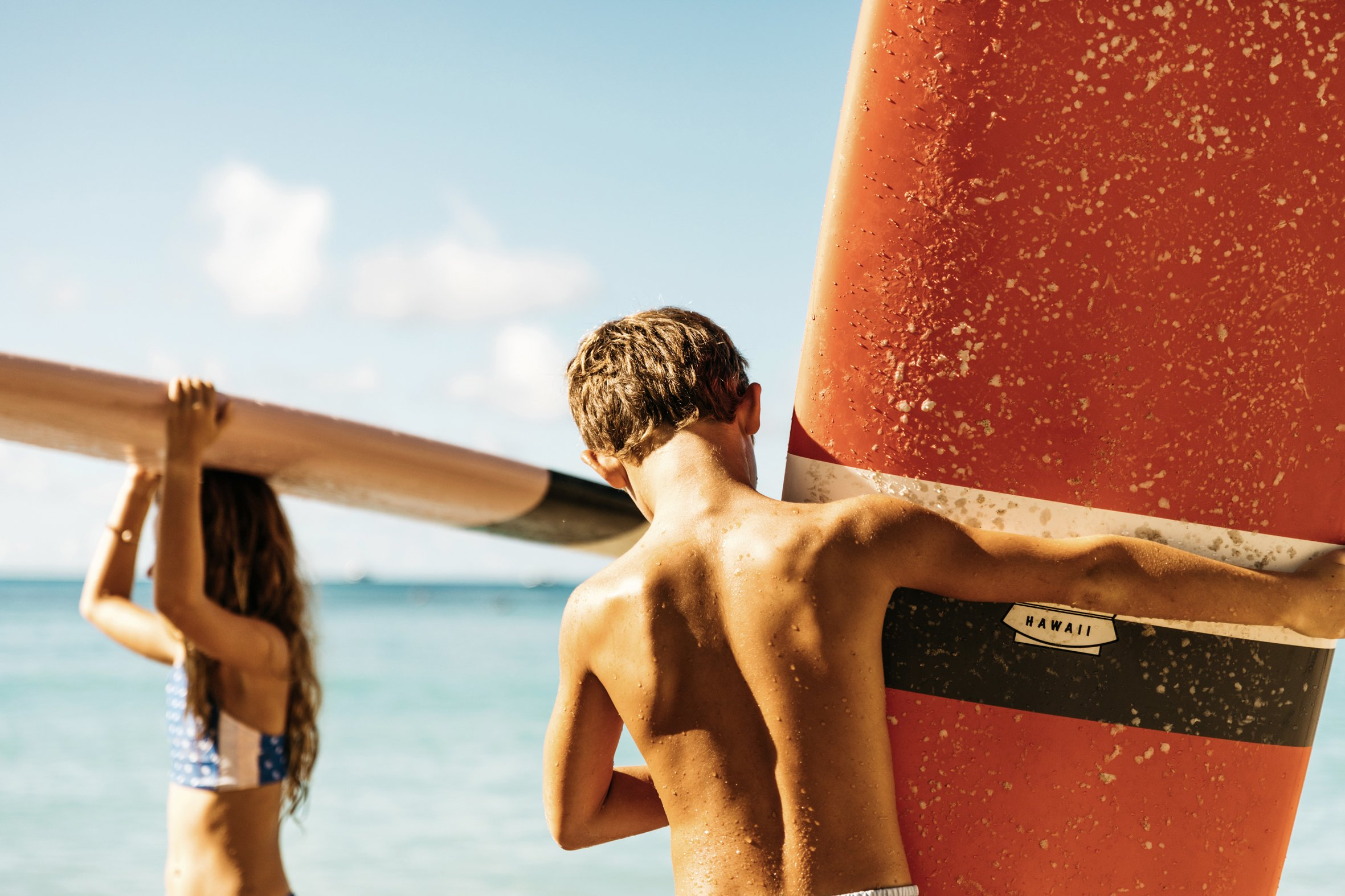 Two kids carry surfboards on the beach in Hawaii.