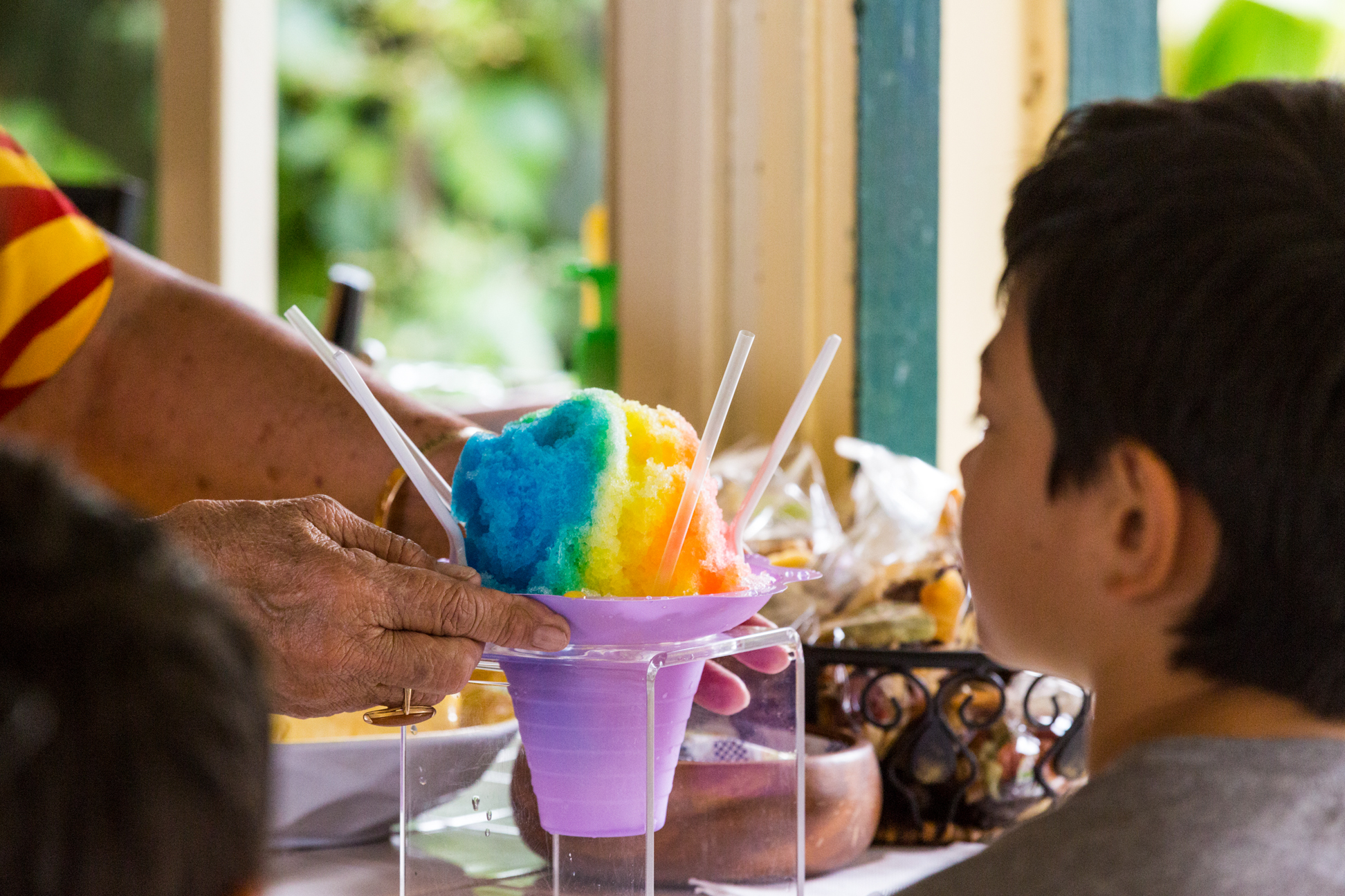 A boy is served a colorful shave ice.