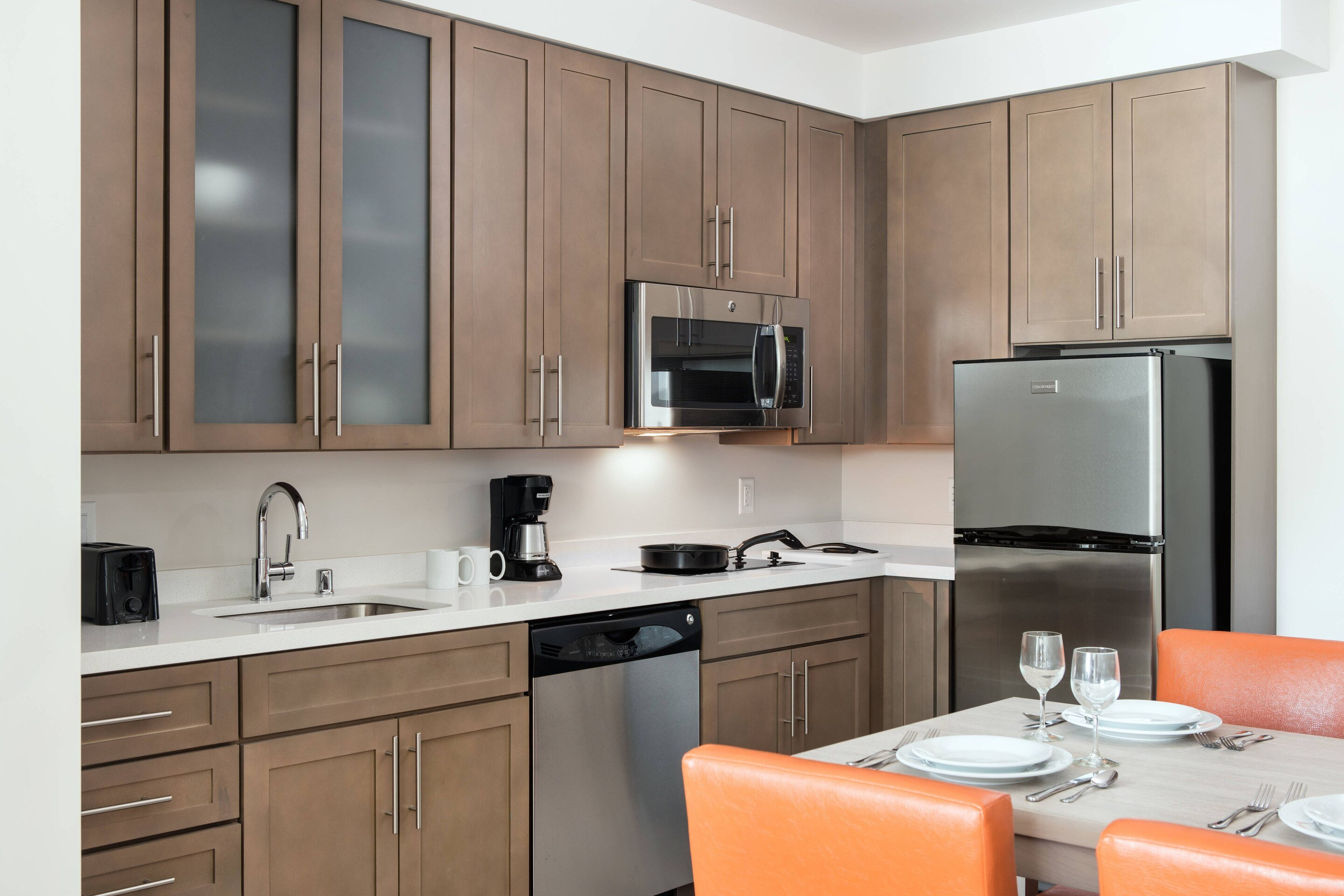 A large decent-sized kitchen with dining table inside one of the Residence Inn San Diego Downtown/Bayfront Suites.