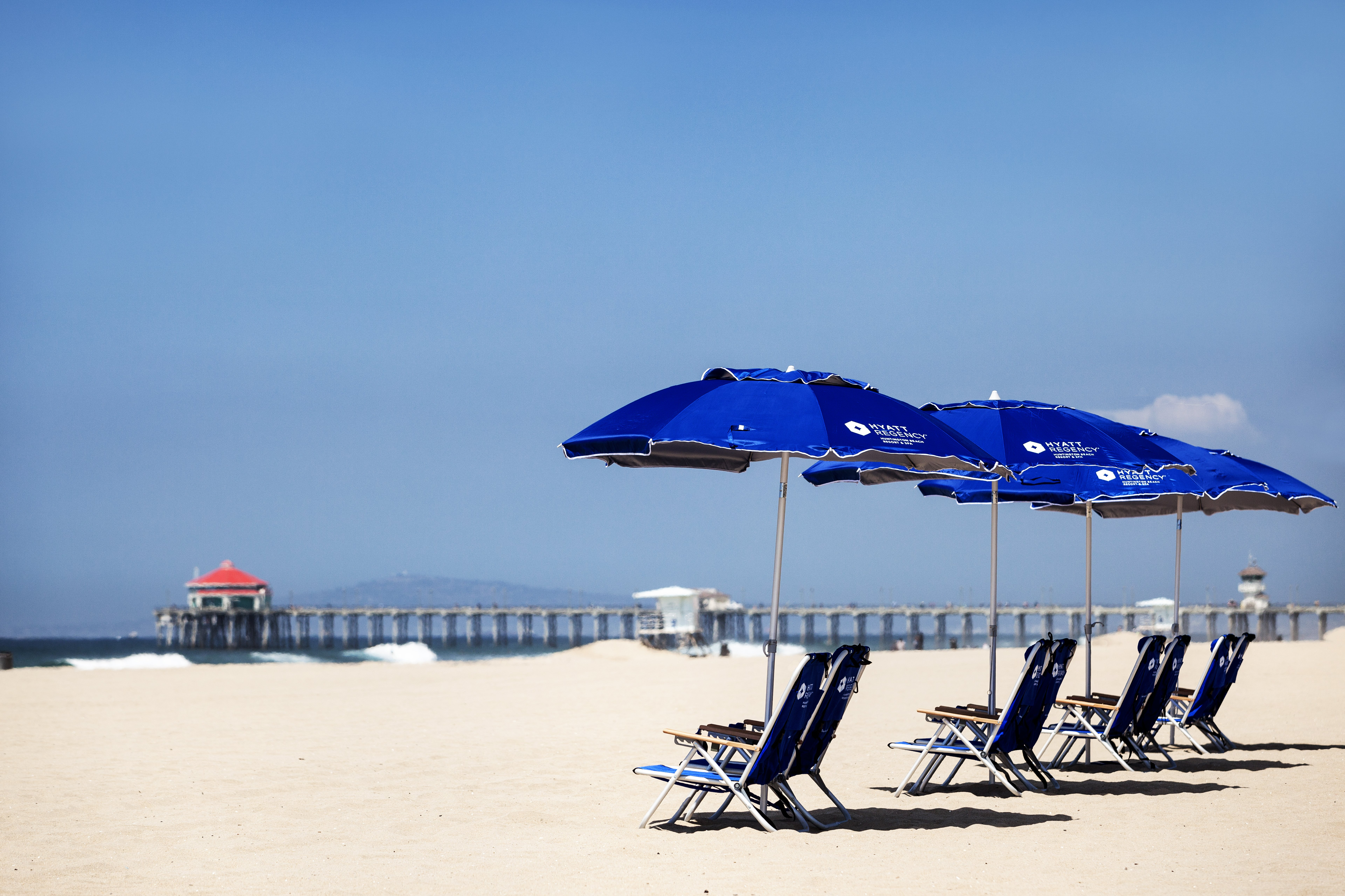 Hotel chairs and umbrellas set in the sand in front of Hyatt Regency Huntington Beach.