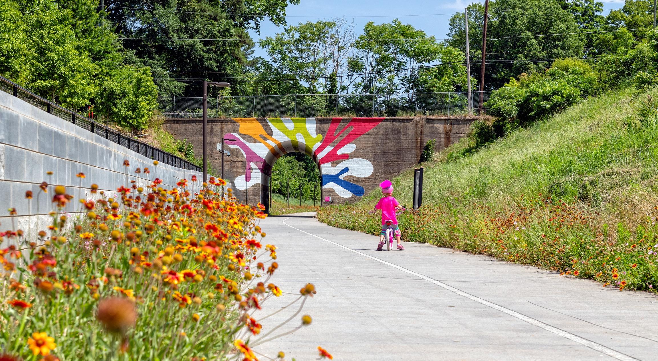 A little girl rides a bike toward a tunnel on The Atlanta Beltline.