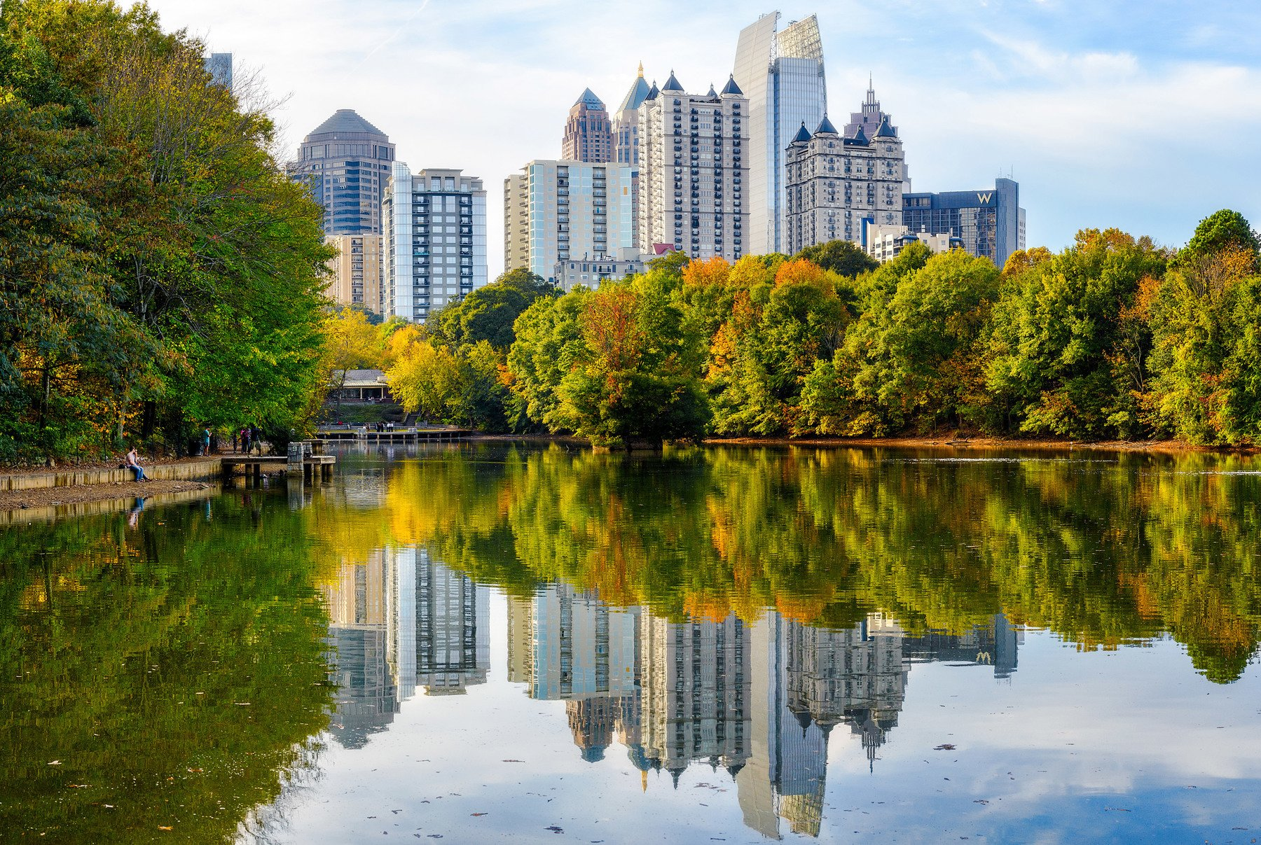 Midtown Atlanta buildings reflect off a lake at Piedmont Park.