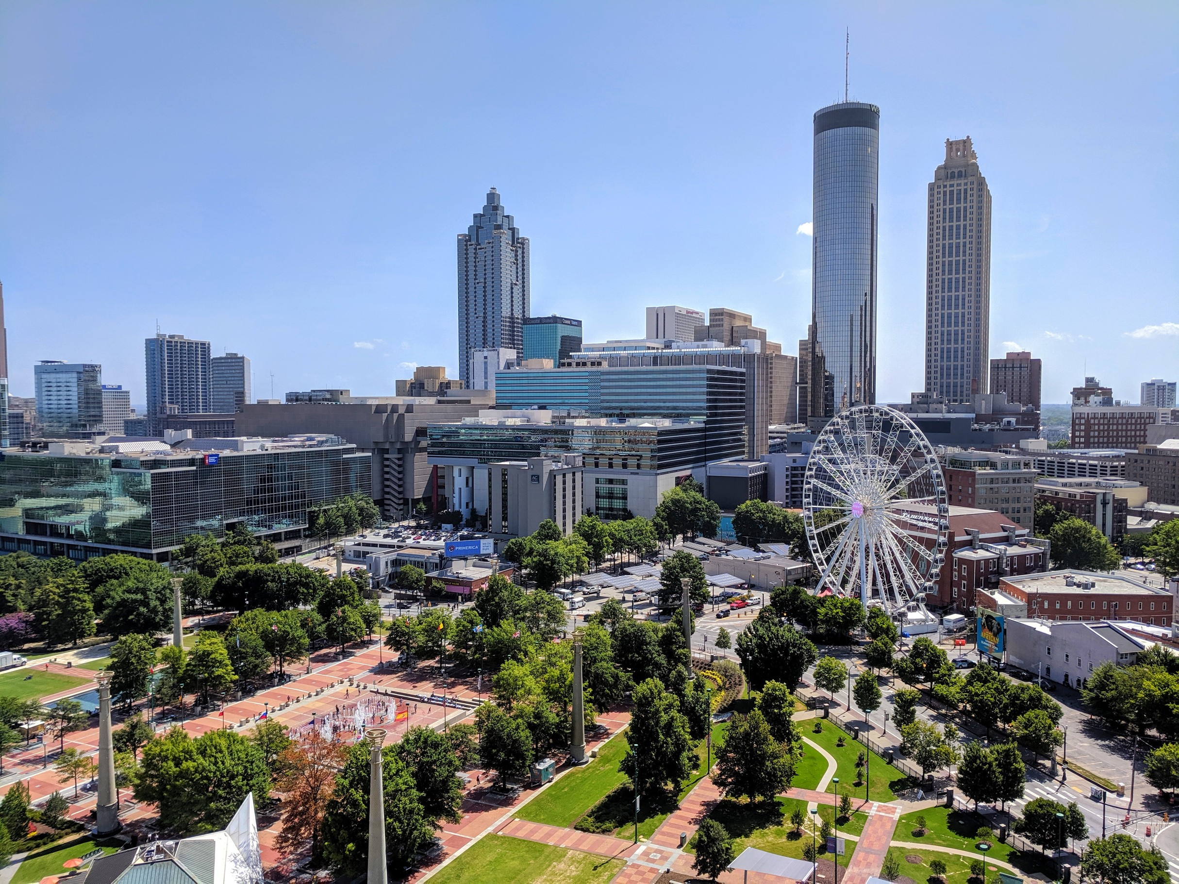 Aerial view of Centennial Olympic Park and Ferris Wheel with skyscrapers in the background.